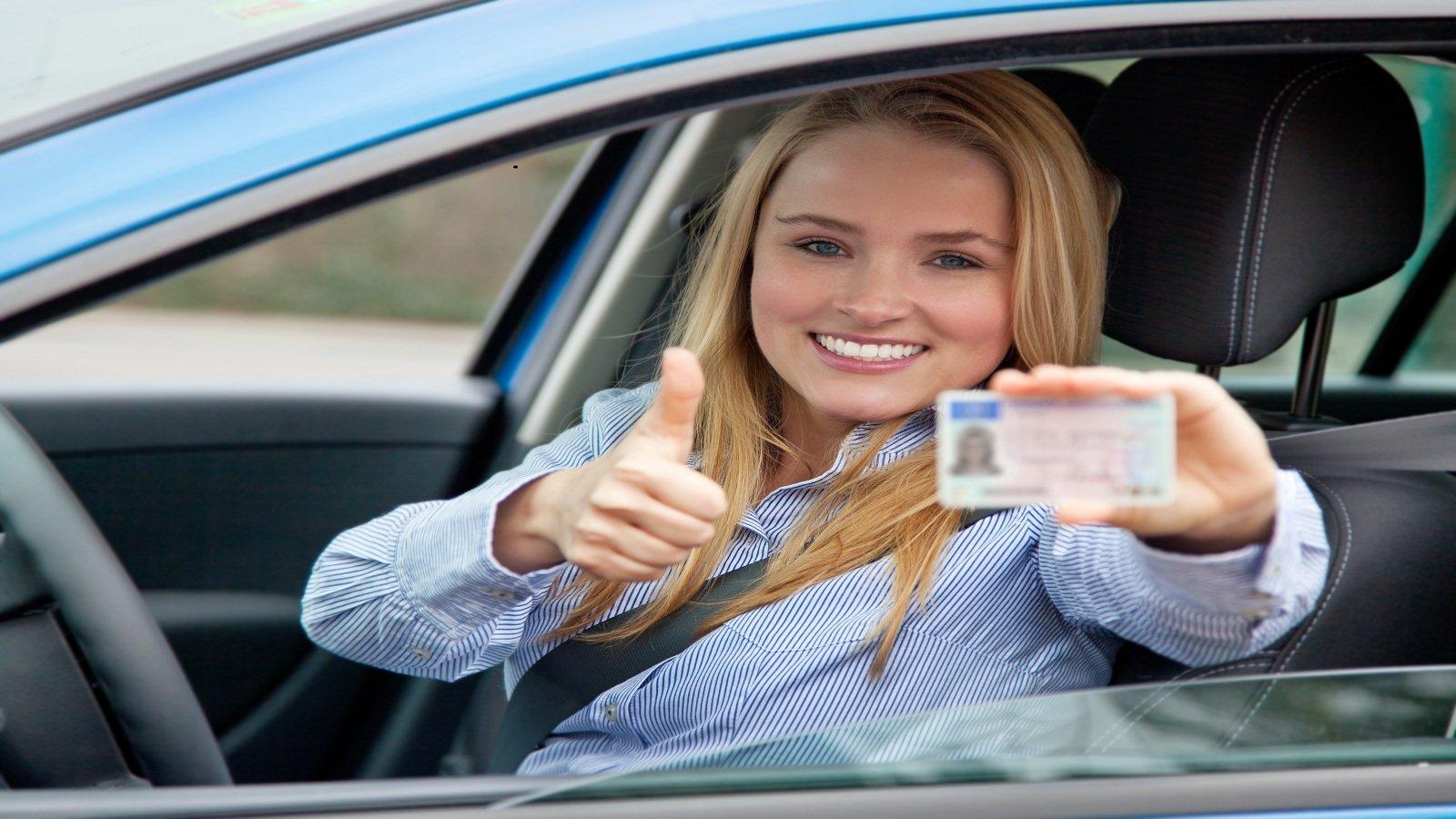 una ragazza in macchina con il pollice in su mentre mostra la patente