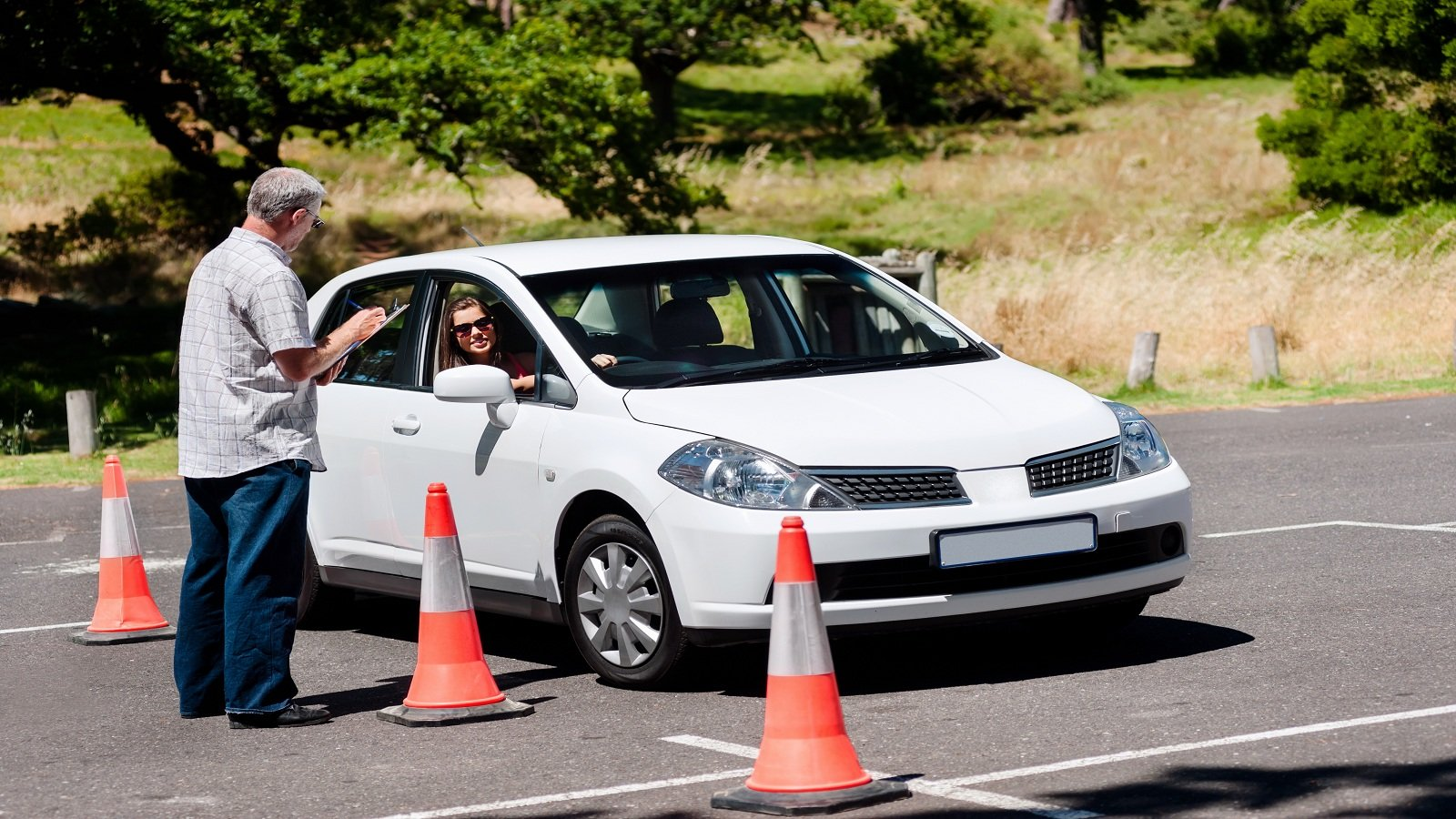 un uomo in piedi che scrive su un quaderno e una ragazza in macchina