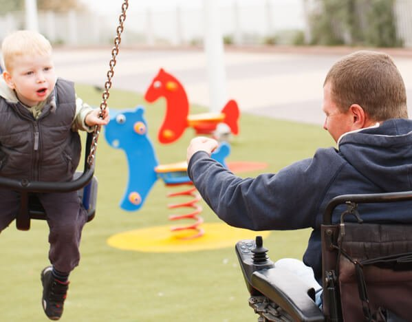 Man in a wheelchair pushing his son on a swing