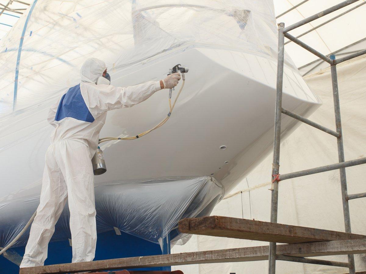 Man spraying a boat in epoxy coating