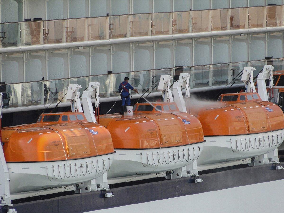 Workmen cleaning hydraulic boat hoists