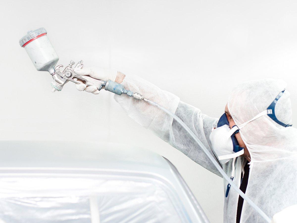 Man priming metal work for spraying