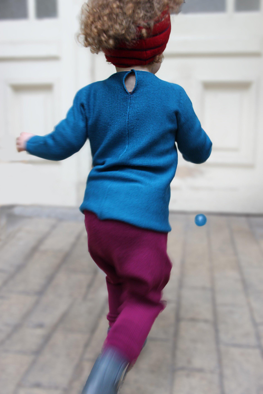 Kleinkind mit gestricktem petrolfarbenen Pullover und Strickhose