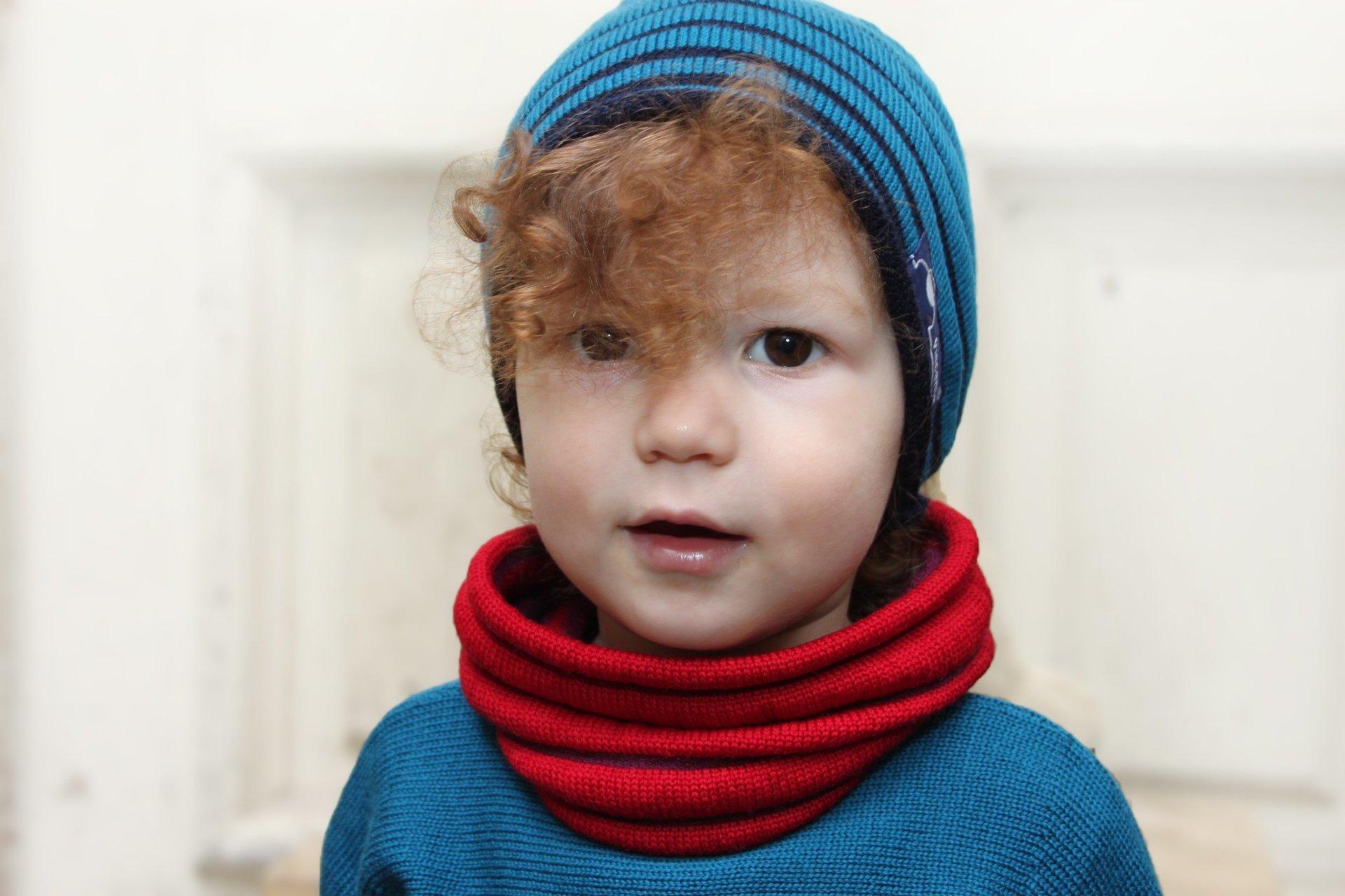 Kind mit Rinkelmütze, die man auch als Schal tragen kann, gestrickt aus Merinowolle
