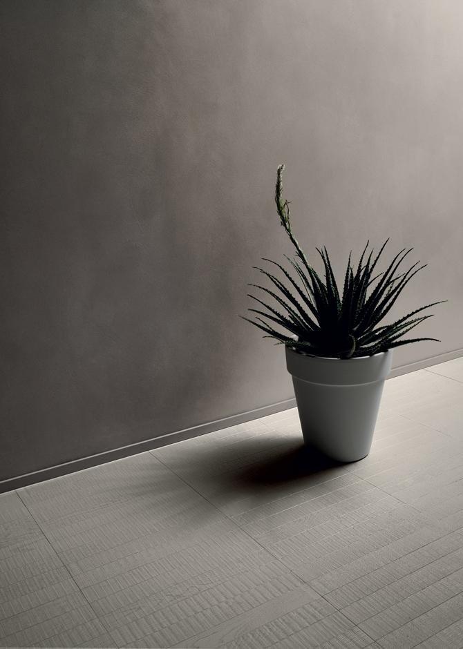 Vaso con pianta di aloe su suolo di piastrelle bianche con disegni rettangolari