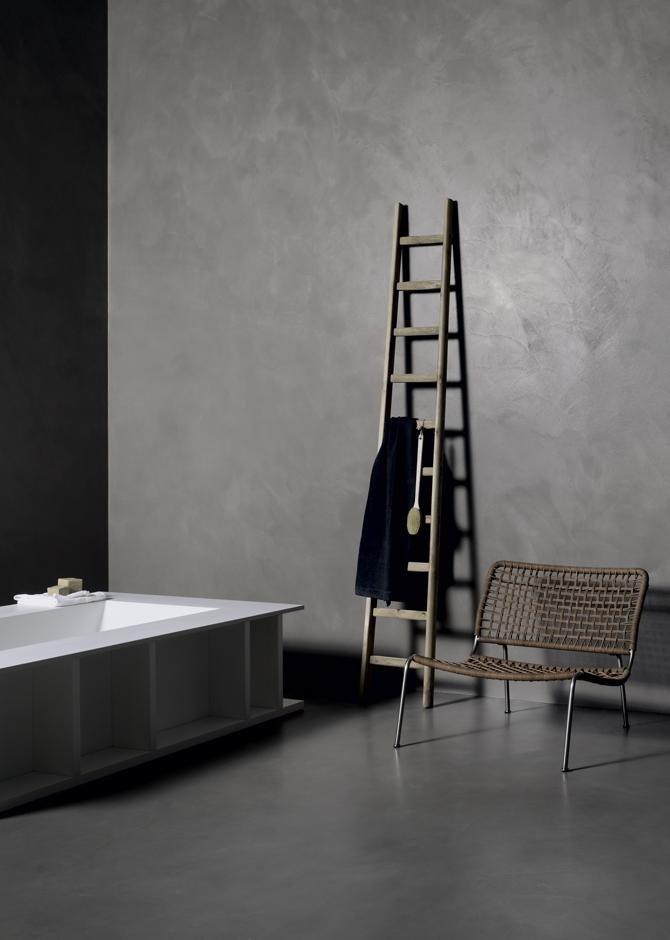 Bagno con pavimento di cemento, vasca originale   e scale che serve di attaccapanno