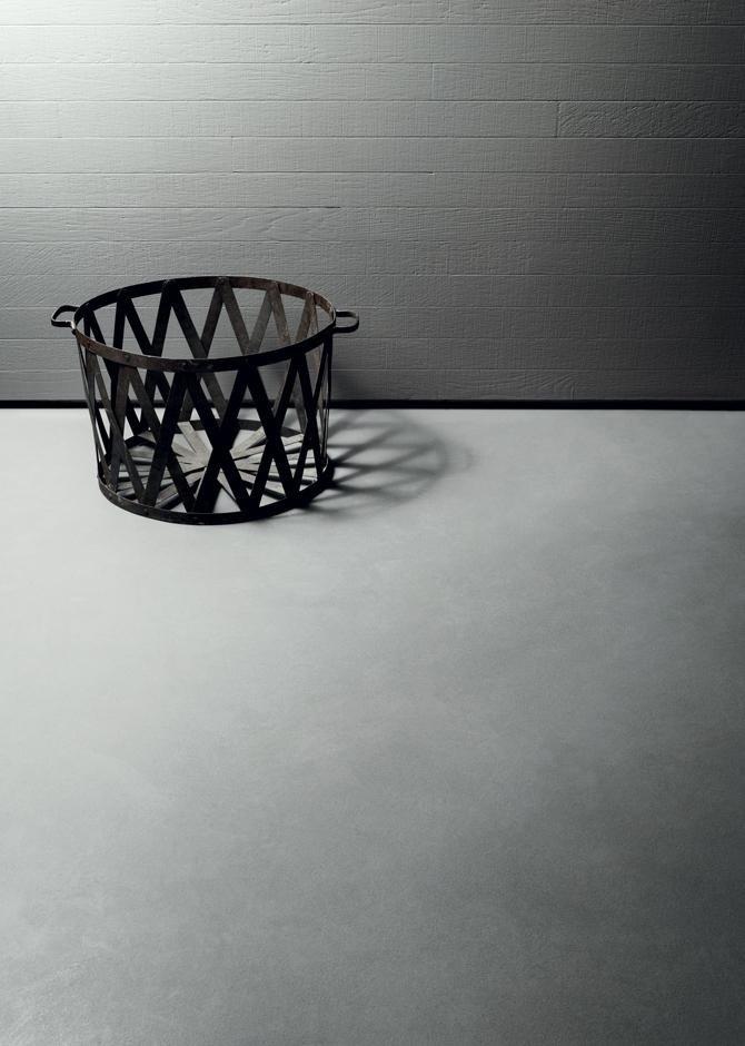 Portavaso di rombi in metallo accanto a parete di mattoni dipinto di grigio