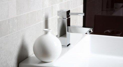 Vaso bianco accanto a rubinetto di acciaio quadrato