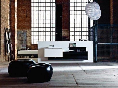 Stanza di artista con due sedili neri e mobile di lavandino in mezzo del soggiorno