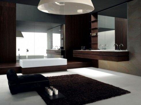Bagno con tappeti e divano bruni, vasca con specchio e mobile in legno con doppio lavandino