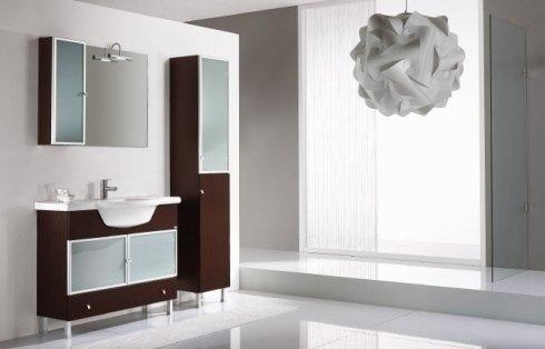 Bagno con mobili in legno scuro e vetro
