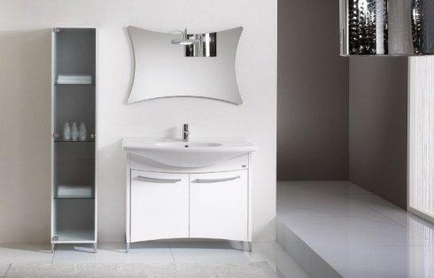 Bagno con mobili bianchi e specchio a forma di fuso