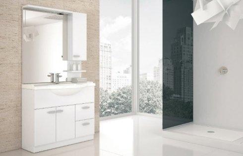 Bagno con mobili bianchi e la parete divisoria di vetro scuro per la doccia