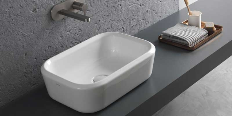 Parete di cemento, lavandino rettangolare e rubinetto incassato nella parete
