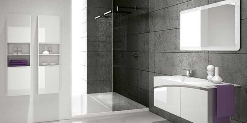 Bagno con grandi piastrelle di pietra, parete divisoria di vetro per la doccia e mobili bianchi