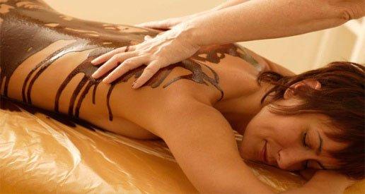 una donna sdraiata a pancia in giù e un'estetista mentre applica del cioccolato sulla schiena