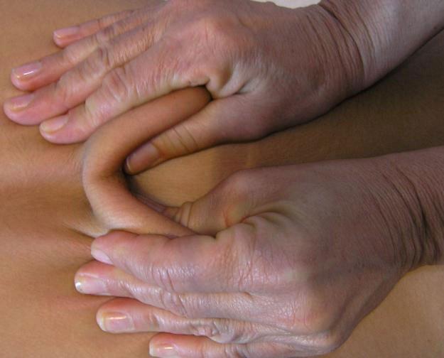Due mani che massaggiano la schiena di una donna vista da vicino