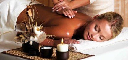 Due mani che massaggiano la schiena di una donna e accanto delle candele