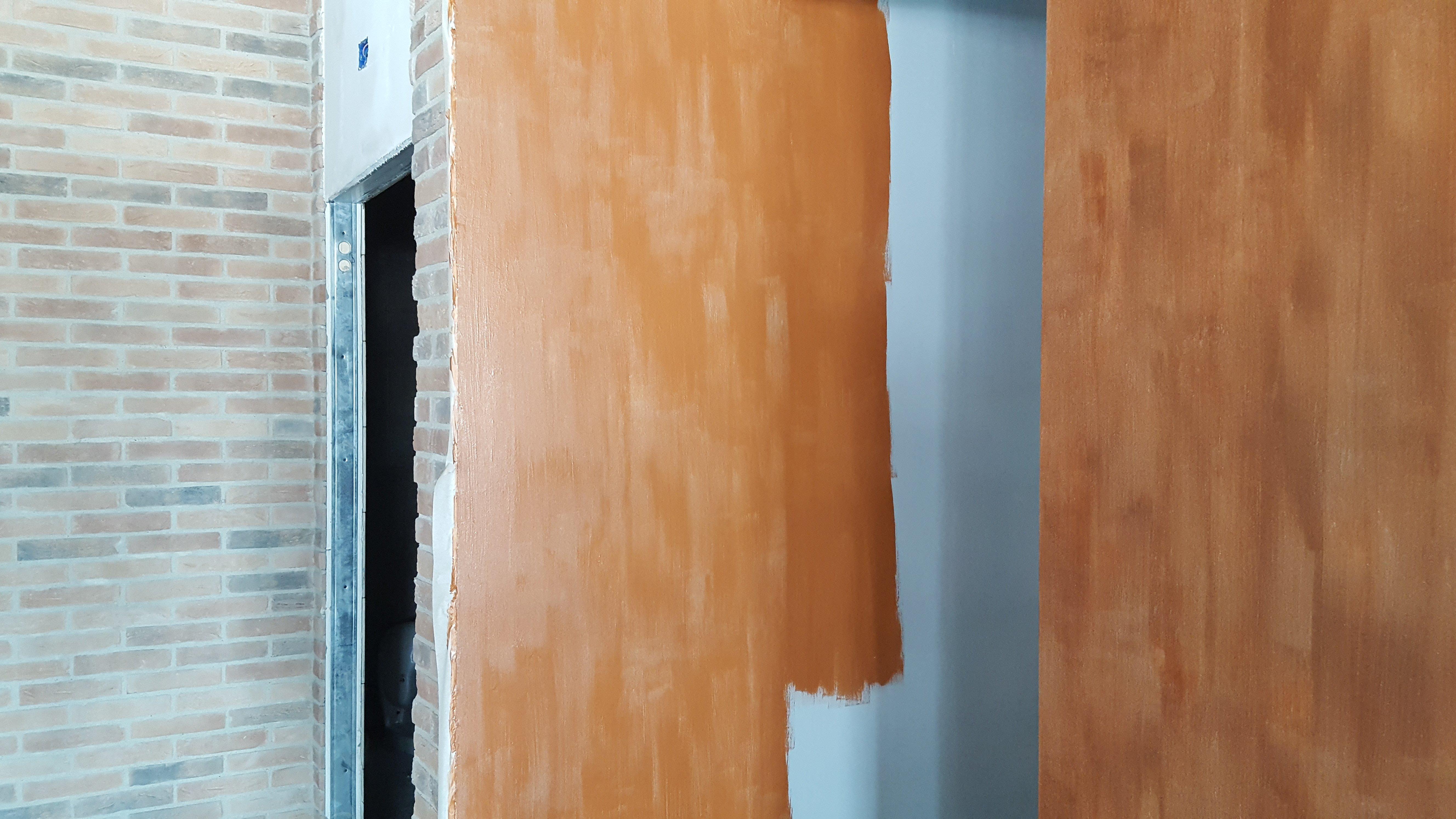 parete azzurra che viene coperta con pittura marrone
