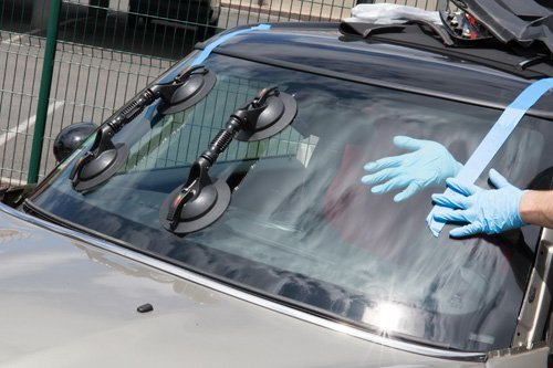 Professional installing a new windscreen on a car