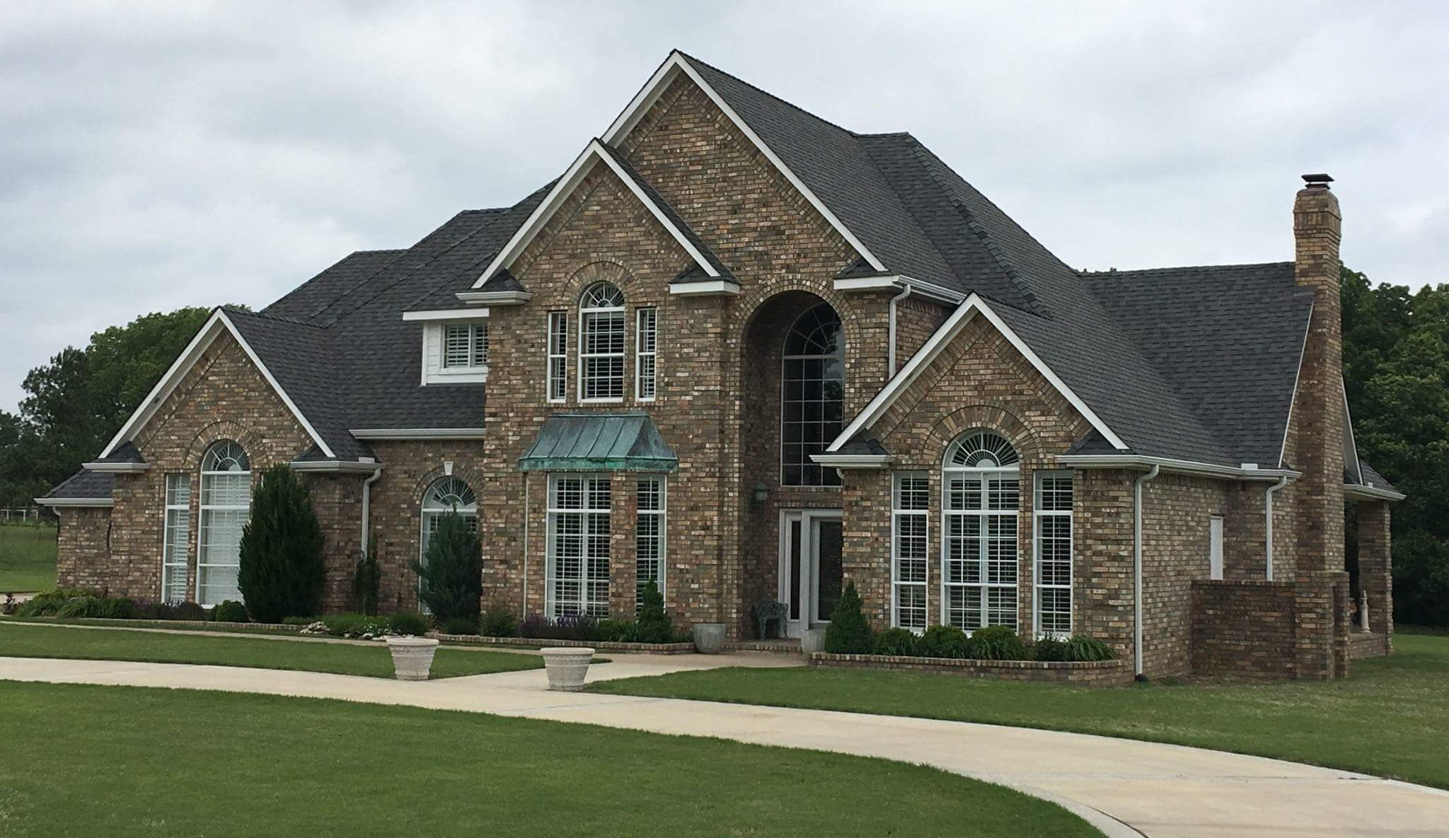 white house with black tiled roof installed by roofing contractors of Jenks, OK