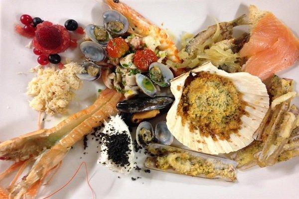un piatto con capesante,cozze,vongole,salmone ,scampi e lamponi