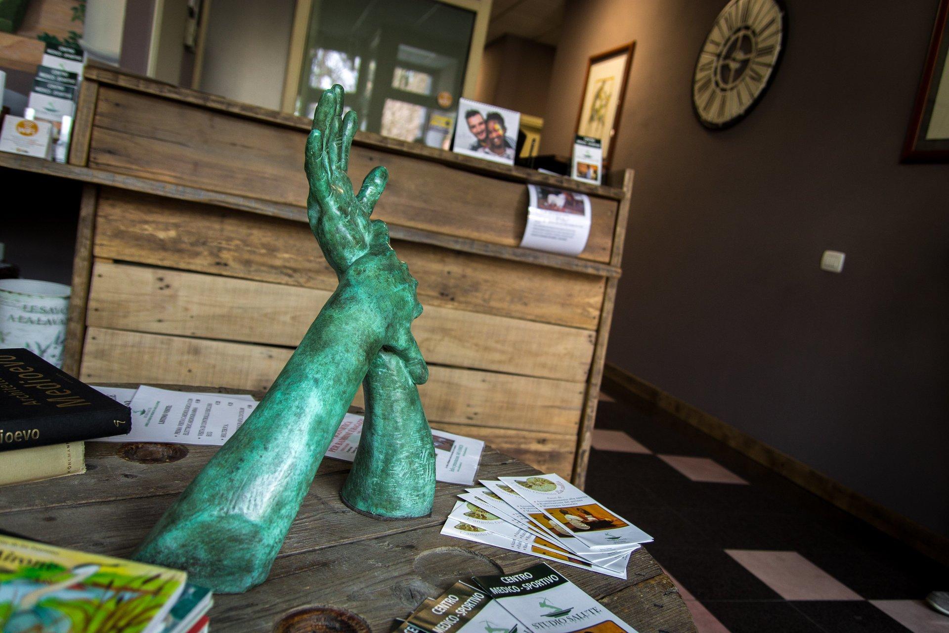 scultura di due mani sopra un tavolo nella sala d'attesa