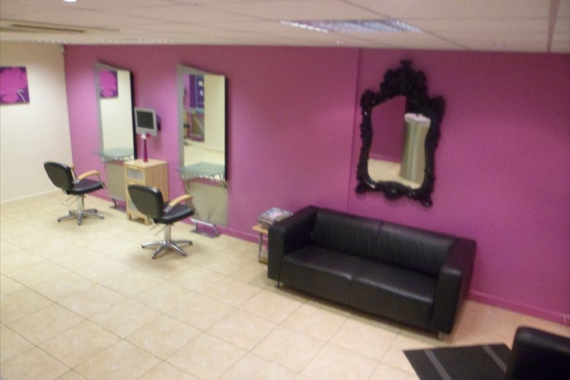 two seater client sofa against pink salon wall
