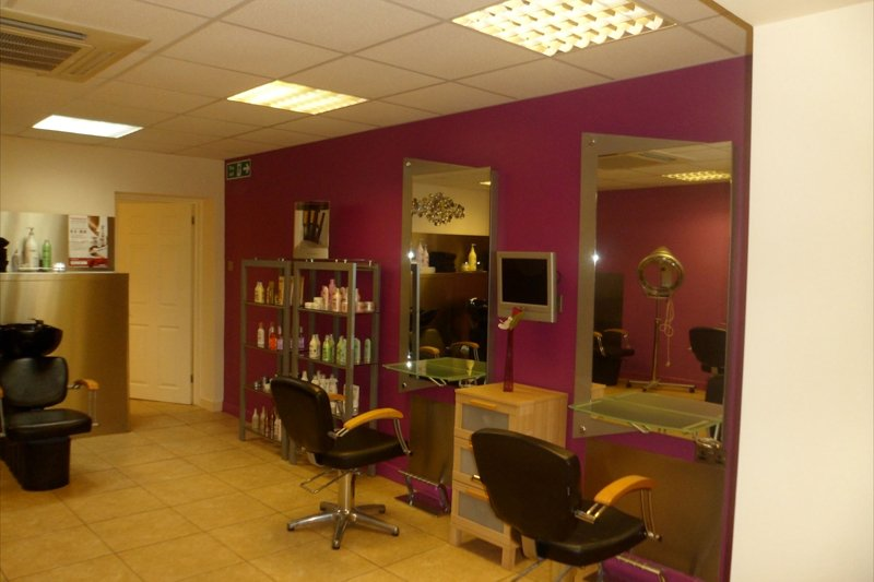 two chairs in salon facing pink wall with mirrors