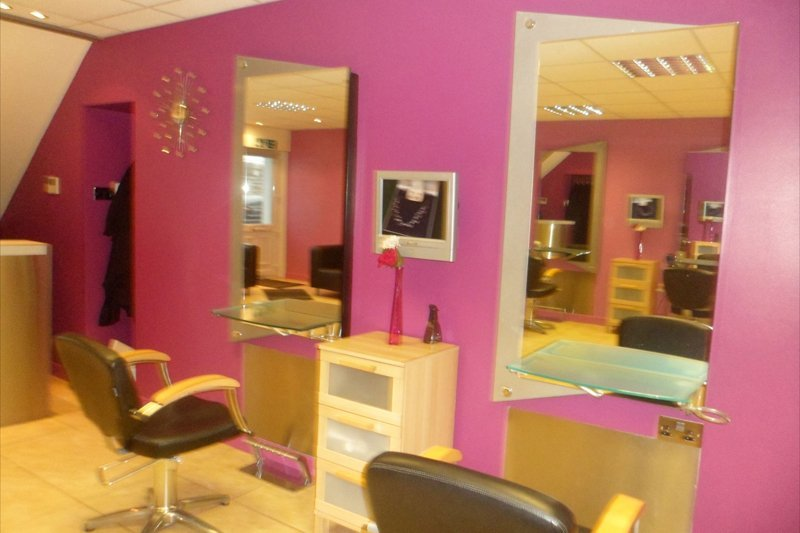 pink salon wall with two chairs and mirrors