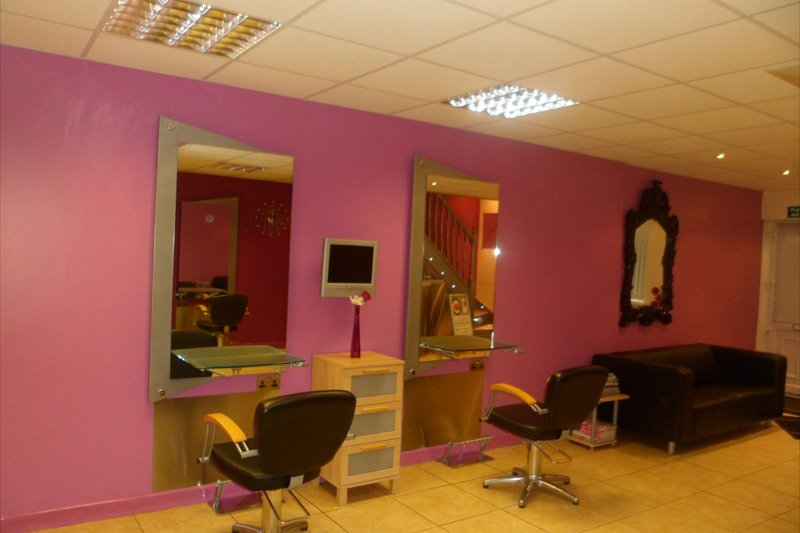 pink and gold themed salon with two styling chairs