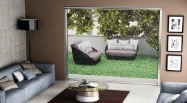 divani, cuscini, tavolo in vetro e arredamento con un giardino