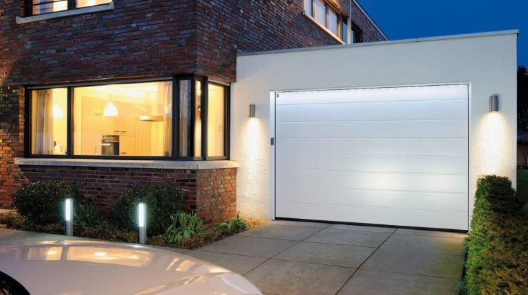 garage bianco vicino a una casa con finestre a vetri