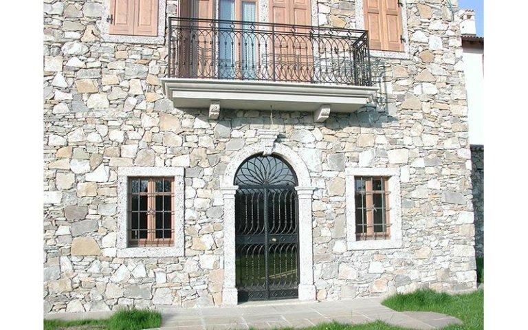 costruzione in sassi con un portone due finestre e una terrazza
