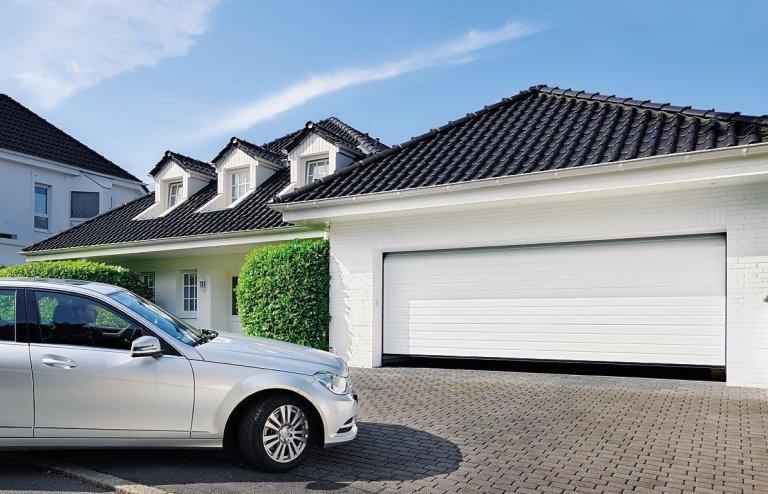 vista laterale di macchina bianca parcheggiata davanti a un garage