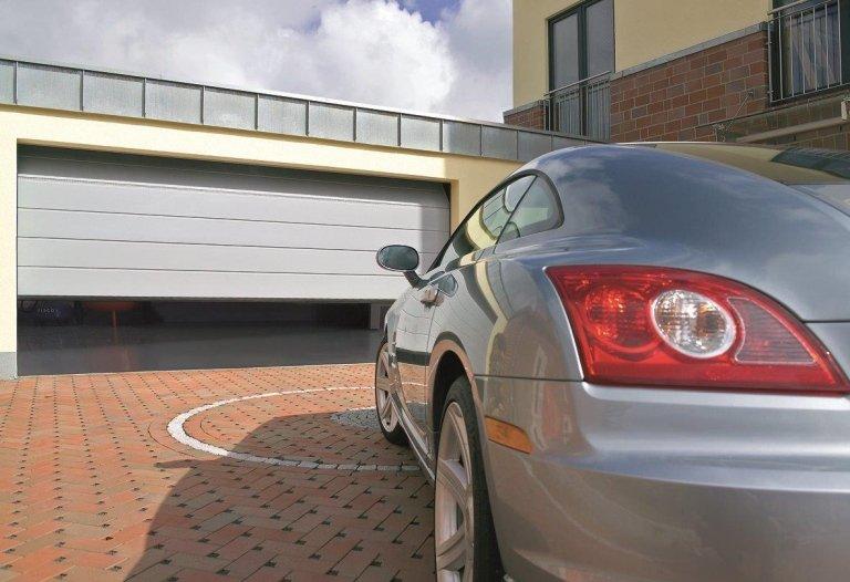 macchina parcheggiata davanti di una garage semi aperto