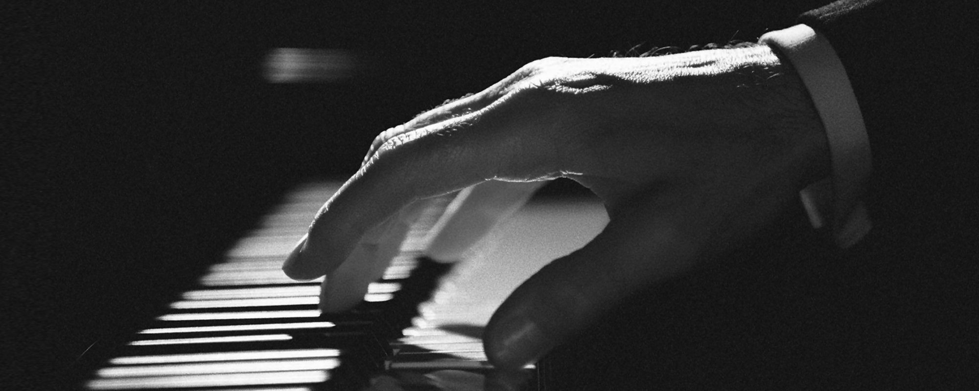 A hand resting on piano keys