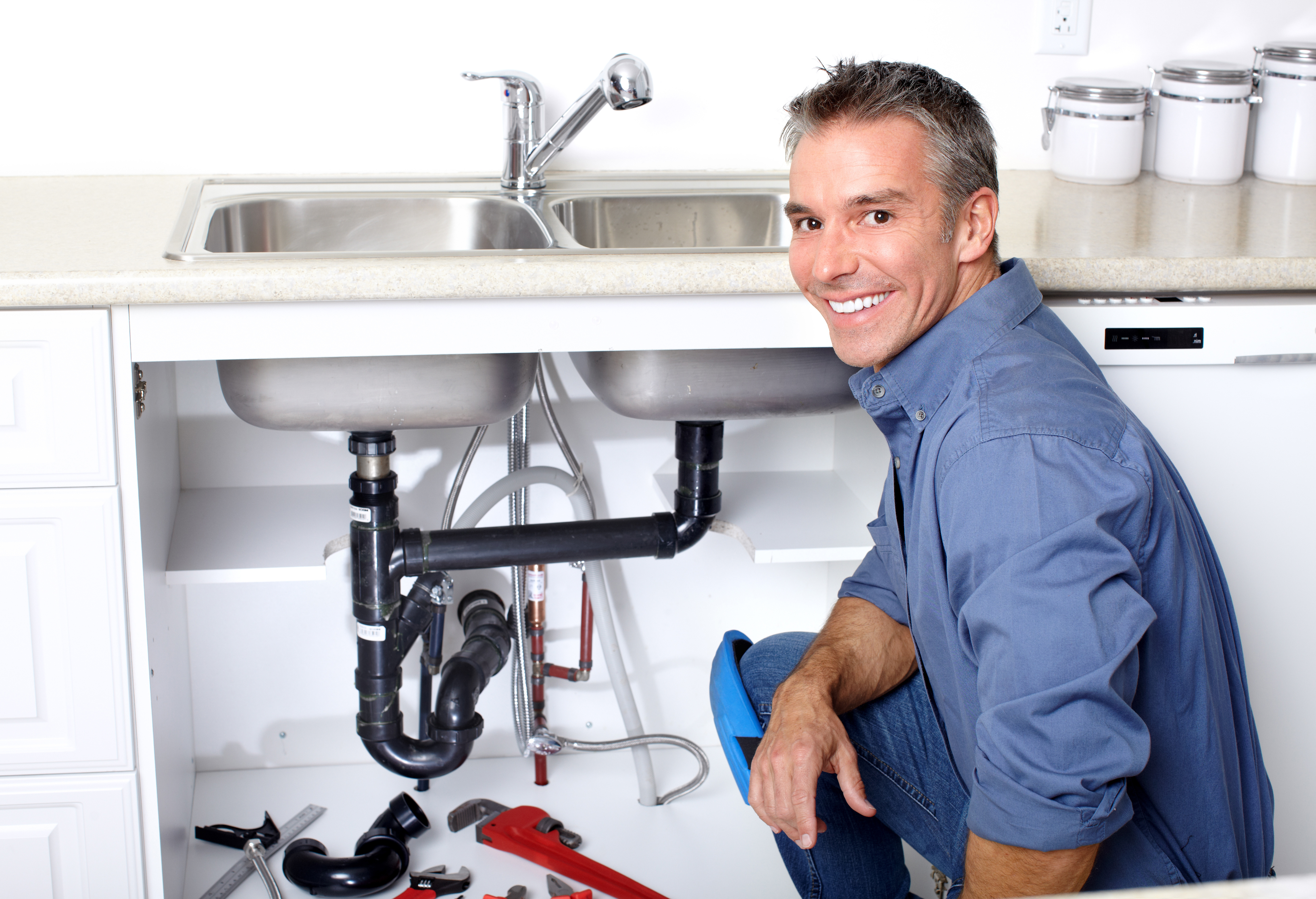 Smiling plumber repairing a sink in a client's home