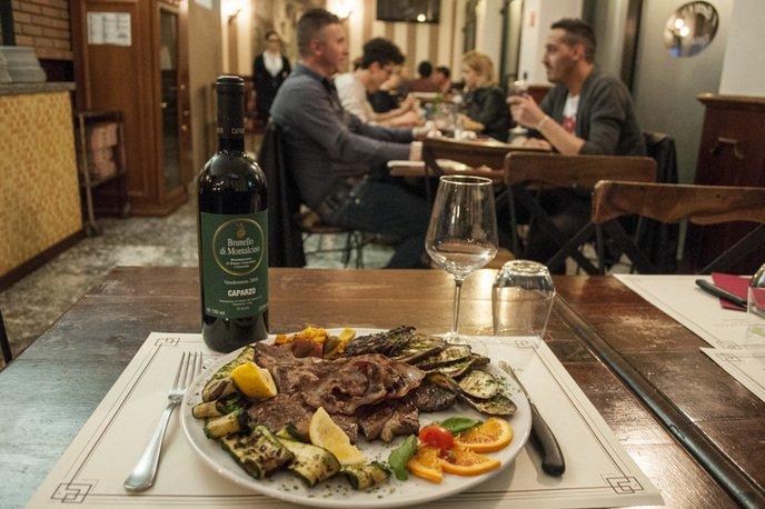 un piatto di carne e verdure , un bicchiere, le posate e una bottiglia di vino