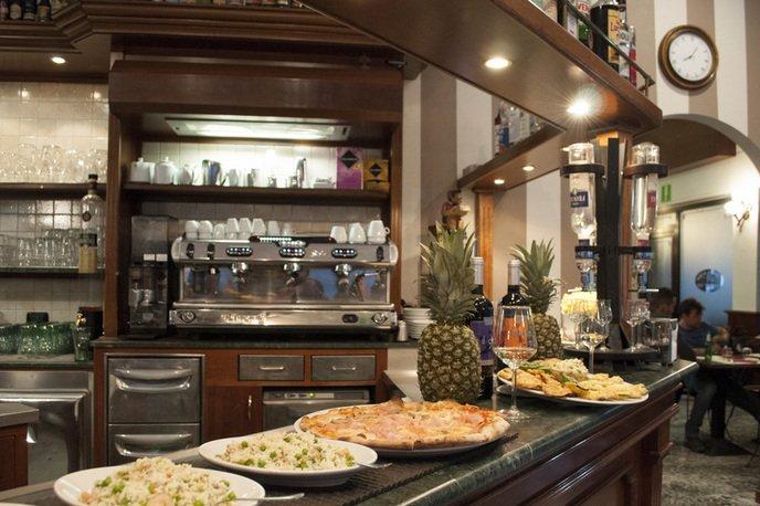il bancone del bar con dei piatti, delle ananas, bicchieri e vista della macchina del caffe