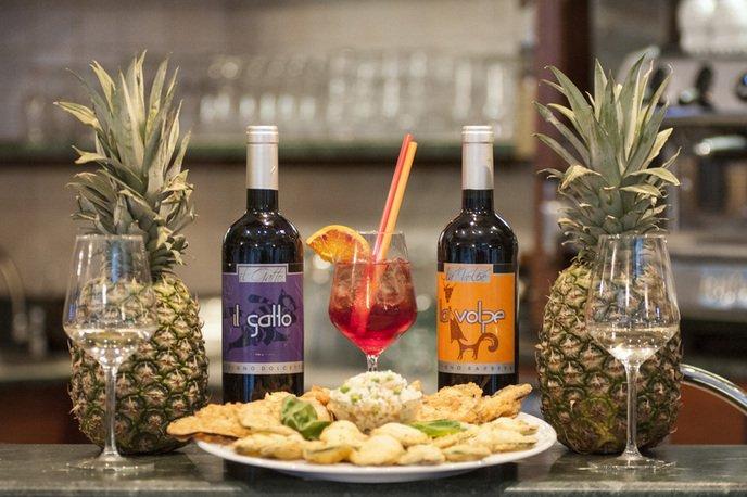 un piatto di salatini, due bicchieri, delle ananas, un cocktail e due bottiglie