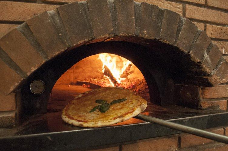una pizza che sta per essere infornata