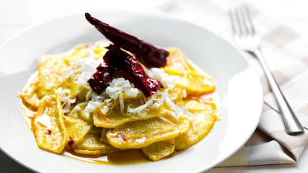 un piatto di ravioli con scaglie di grana e del radicchio rosso