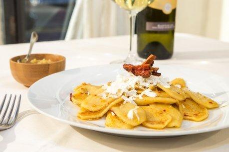 un piatto di ravioli con scaglie di grana, sul tavolo una ciotola di legno con dentro del cibo e una bottiglia di vino
