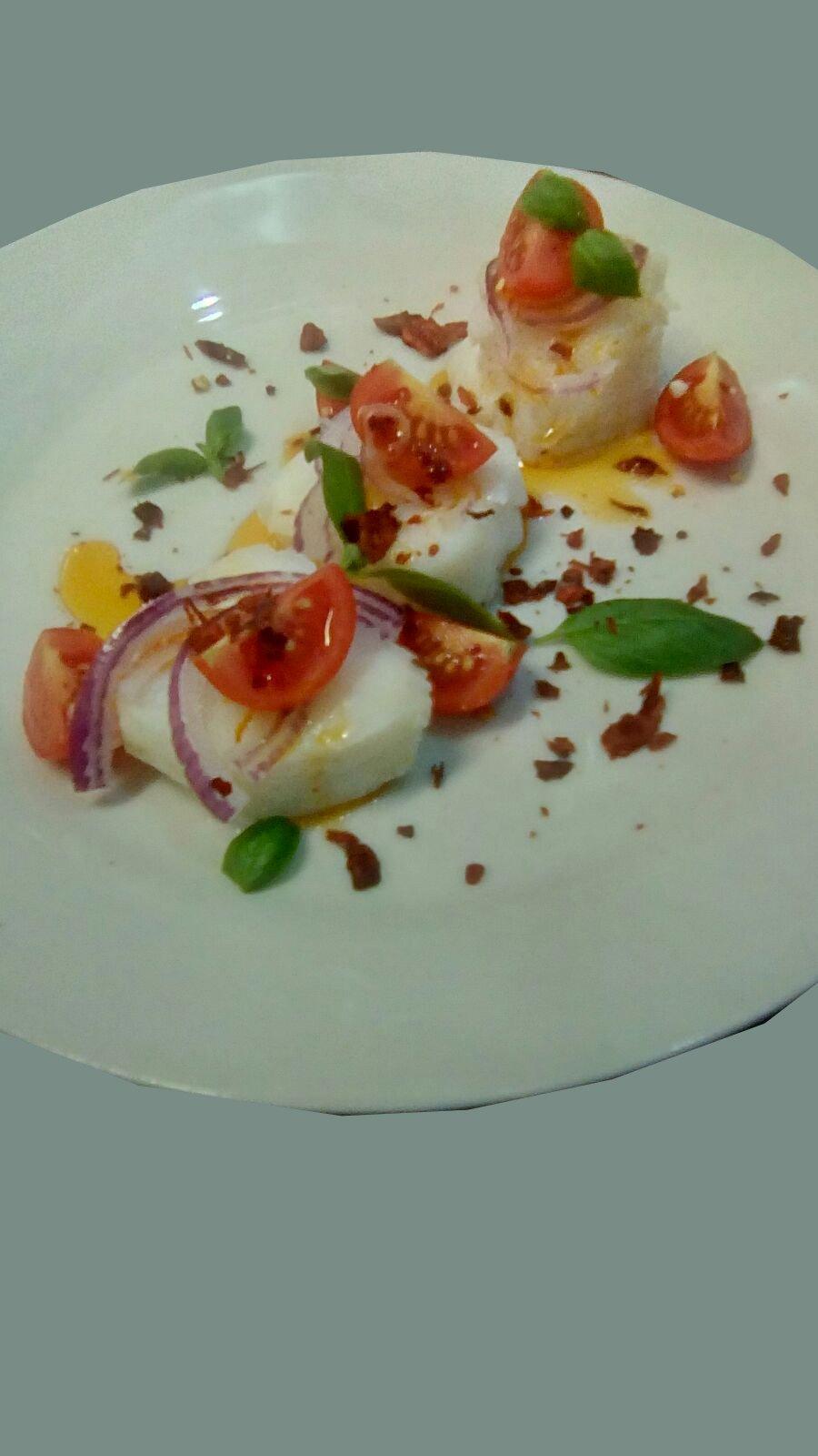 un piatto a base di pesce con pomodori,cipolle e basilico