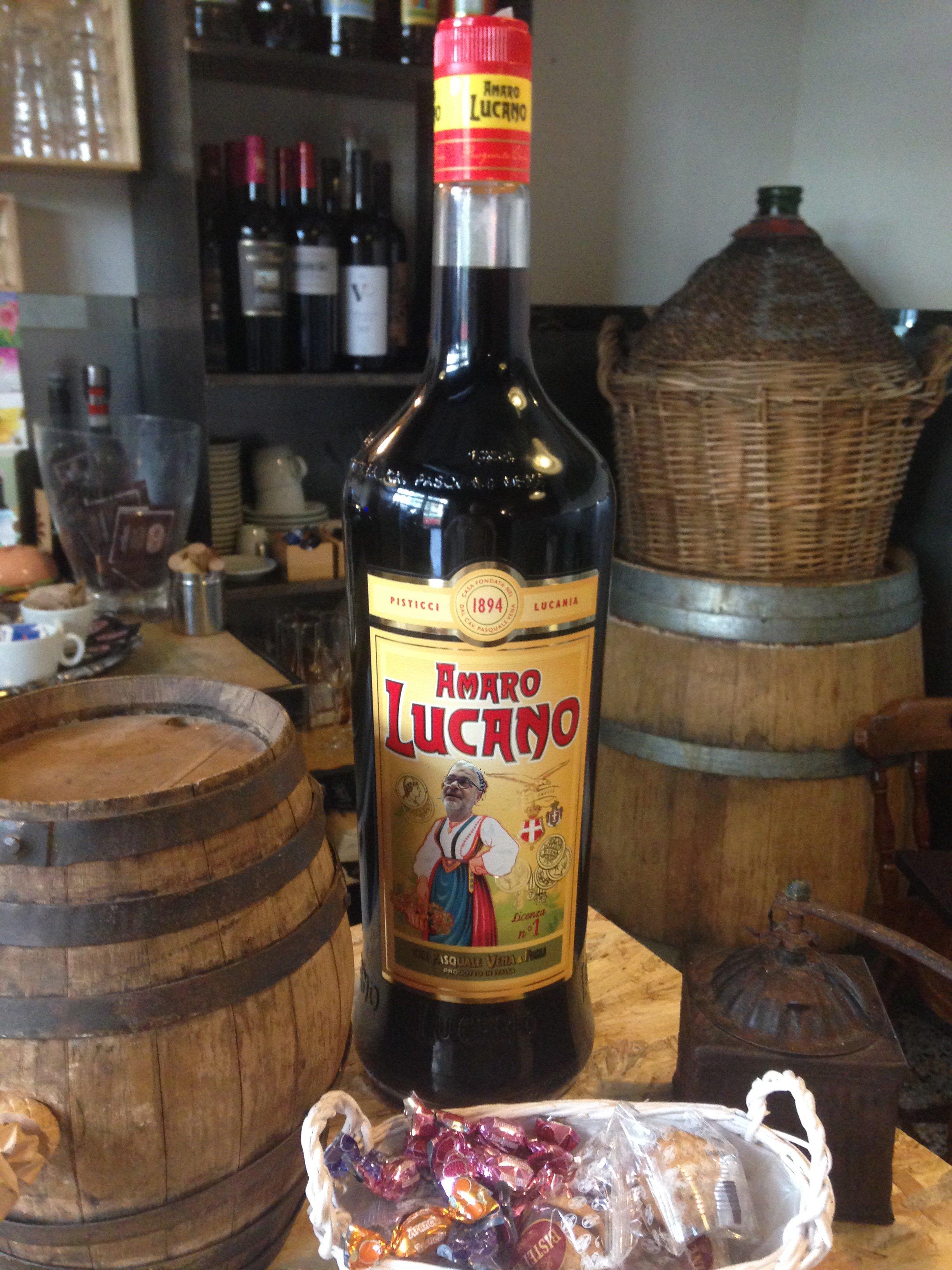 un bottiglia di amaro Lucano e dei barili di legno accanto