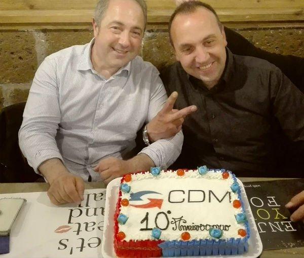 Due uomini vicino a una torta con scritto Cdm