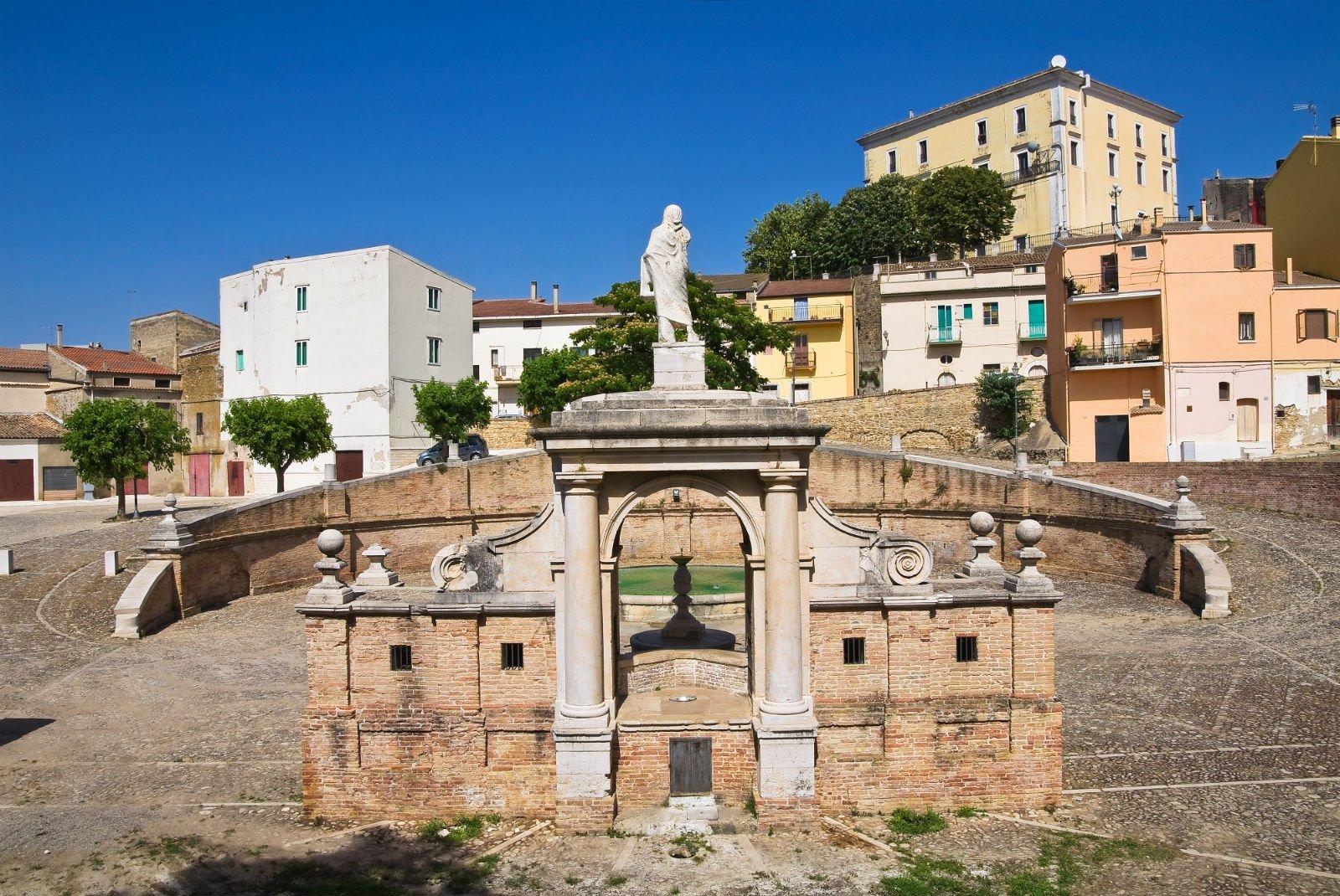 Statua, fontana e case sullo sfondo