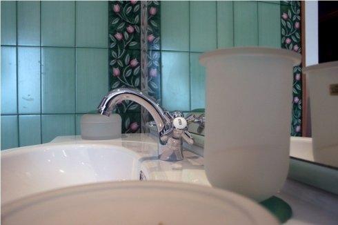 rubinetto in acciaio e piastrelle verdi