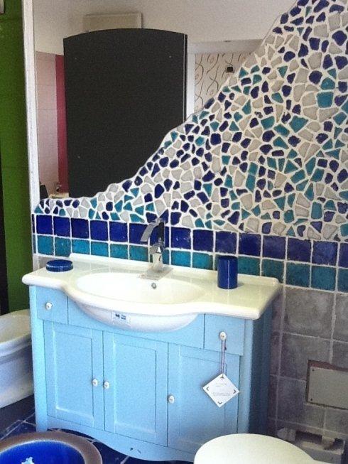 lavabo con mobile azzurro e parete di piastrelle a mosaico